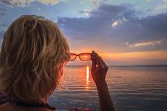 Blonde Frau, welche die Sonne betrachtet Stockbild
