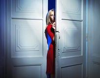 Blonde Frau, welche sorgfältig die Tür öffnet Lizenzfreie Stockfotos