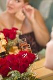 Blonde Frau wendet Make-up am Spiegel nahe Champagne und Rosen an Stockbilder
