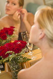 Blonde Frau wendet Make-up am Spiegel nahe Champagne und Rosen an Lizenzfreie Stockfotos