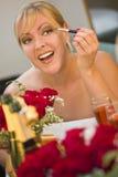 Blonde Frau wendet Make-up am Spiegel nahe Champagne und Rosen an Stockbild