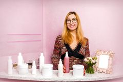 Blonde Frau wirft mit einer Flasche Kosmetik auf Lizenzfreies Stockfoto