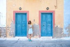 Blonde Frau Yound an der typischen griechischen traditionellen Stadt mit bunten Gebäuden auf Kastelorizo-Insel, Griechenland Lizenzfreies Stockbild