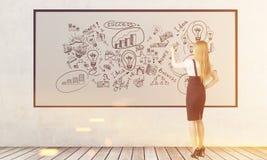 Blonde Frau zeichnet Geschäftsskizzen auf dem whiteboard, getont Lizenzfreie Stockbilder