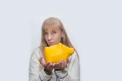 Blonde Frau zeigt gelbes Schwein monebox Lizenzfreies Stockfoto
