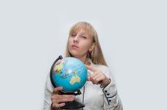 Blonde Frau zeigt Kugel Stockbild