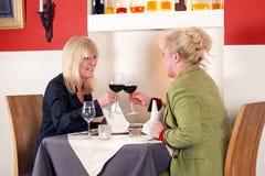 Blonde Frau zwei, die mit Rotwein röstet Lizenzfreie Stockfotos