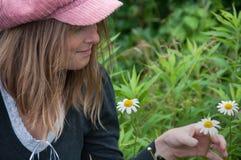 Blonde Frauen-bewundern Frühjahr-Gänseblümchen Lizenzfreie Stockfotografie