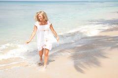Blonde Frauen, die durch das Wasser laufen Stockbild