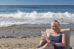 Blonde Frauen, die Tablet am Strand verwenden Stockfoto