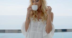 Blonde Frauen-trinkender Kaffee auf Ozean Front Balcony stock footage