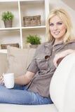 Blonde Frauen-trinkender Tee oder Kaffee zu Hause Stockbild