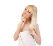 Blonde Frauenholding ihr Haar und Denken Lizenzfreie Stockfotos