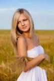 Blonde Frauenholding-Weizengarbe Stockbild