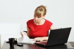 Blonde Frauenlesezeitschrift am Schreibtisch Lizenzfreies Stockfoto