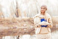 Blonde Frauenlesung im Herbstpark lizenzfreie stockbilder