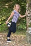Blonde Frauenmitte alterte, Beine in einem Park ausdehnend Lizenzfreies Stockbild