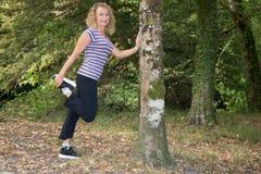 Blonde Frauenmitte alterte, Beine in einem Park ausdehnend Lizenzfreies Stockfoto