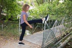 Blonde Frauenmitte alterte, Beine in einem Park ausdehnend Lizenzfreie Stockbilder
