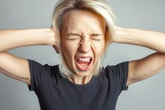 Blonde Frauenschreie, ihre Augen schließend Lizenzfreies Stockbild