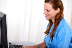 Blonde freundliche Krankenschwester, die zum Computer schaut Lizenzfreies Stockbild