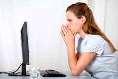 Blonde friendly young lady looking to computer Royalty Free Stock Image