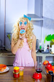 Blonde funny girl on kitchen eating blue dona. Blonde funny girl on kitchen eating blue donut with fashion makeup Stock Photography