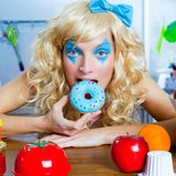 Blonde funny girl on kitchen eating blue dona. Blonde funny girl on kitchen eating blue donut with fashion makeup Royalty Free Stock Photography