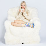 Blonde on furry arm-chair stock photos