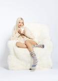 Blonde on furry arm-chair Stock Photos