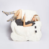 Blonde on furry arm-chair Stock Photo