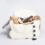Blonde on furry arm-chair Stock Images
