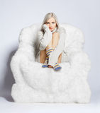Blonde on furry arm-chair Royalty Free Stock Image