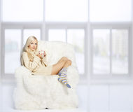 Blonde on furry arm-chair Royalty Free Stock Images
