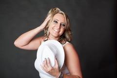Blonde gelockte behaarte Frau, die Hut beim Schlagen einer Haltung hält Stockbilder