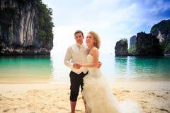 blonde gelockte Braut des Bräutigams im flaumigen Stand schließen sich Händen auf Strand an Lizenzfreie Stockfotos
