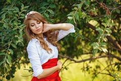 Blonde gelockte Frau, die unter dem Baum steht Lizenzfreies Stockfoto