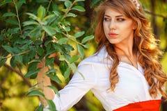 Blonde gelockte Frau, die unter dem Baum steht Lizenzfreie Stockfotografie