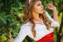 Blonde gelockte Frau, die unter dem Baum steht Stockbild
