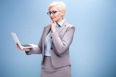 Blonde Geschäftsfrau auf blauem Hintergrund Lizenzfreie Stockfotos