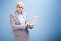 Blonde Geschäftsfrau auf blauem Hintergrund Stockfotos