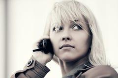 Blonde Geschäftsfrau der jungen Mode, die am Handy im Freien spricht Stockfotografie
