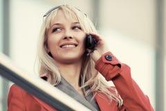 Blonde Geschäftsfrau der jungen Mode, die um Handy ersucht Lizenzfreie Stockfotos