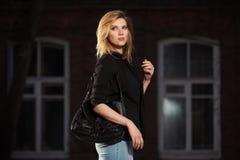 Blonde Geschäftsfrau der jungen Mode mit Handtasche gehend in Nacht Lizenzfreie Stockbilder