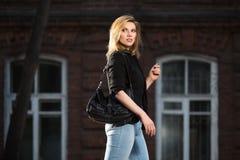 Blonde Geschäftsfrau der jungen Mode mit Handtasche gehend in Nacht Stockfotografie