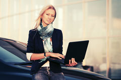 Blonde Geschäftsfrau der jungen Mode mit Laptop durch ihr Auto Stockfotografie