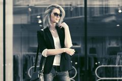 Blonde Geschäftsfrau der jungen Mode in der Sonnenbrille im Einkaufszentrum Stockfoto