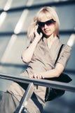 Blonde Geschäftsfrau der Mode, die um Handy ersucht Lizenzfreie Stockbilder