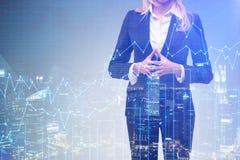 Blonde Geschäftsfrau in der Nachtstadt mit blauen Diagrammen Stockfotos