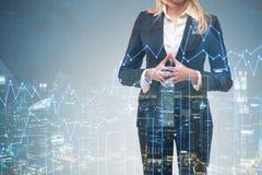 Blonde Geschäftsfrau in der Nachtstadt mit Diagrammen Lizenzfreies Stockfoto